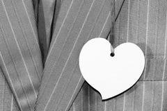 Bedrijfsmensen` s grijs kostuum met een prijskaartje in de vorm van een hart Stock Afbeelding
