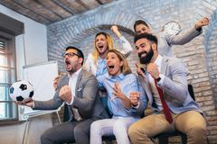 Bedrijfsmensen of voetbalventilators die op voetbal op TV letten en overwinning vieren Vriendschap, sporten en vermaakconcept stock foto's