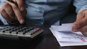Bedrijfsmensenaccountant die berekeningen maken die gegevens schrijven en nota's nemen stock videobeelden