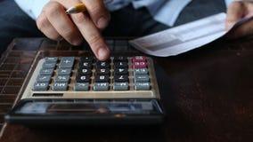Bedrijfsmensenaccountant die berekeningen maken die gegevens schrijven en nota's nemen stock footage
