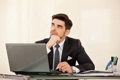 Bedrijfsmensendagdromen bij zijn bureau Stock Afbeelding
