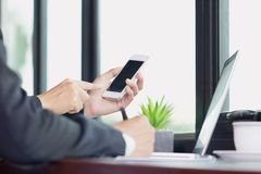 Bedrijfsmensenhand die aan slimme telefoon en laptop computer werken stock fotografie