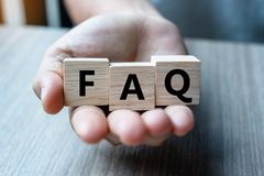Bedrijfsmensenhand die houten kubus met FAQ-tekstveelgestelde vragen houden op lijstachtergrond Financieel, op de markt brengend  royalty-vrije stock foto