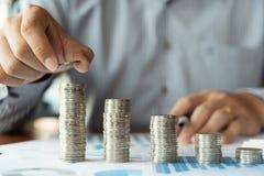 Bedrijfsmensenhand die muntstukstapel voor het geldinvestering van de begrotingsbesparing en financiële boekhouding beheers of he royalty-vrije stock foto's
