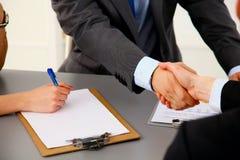 Bedrijfsmensenhanddruk, die bij de lijst zitten Stock Afbeeldingen