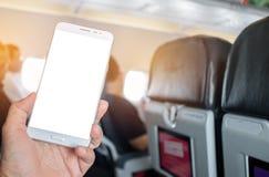 Bedrijfsmensenhanden die gebruiks slimme telefoon in vliegtuig houden blurre Stock Afbeelding