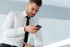 Bedrijfsmensenlezing iets op het Scherm van Zijn Celtelefoon Royalty-vrije Stock Foto's