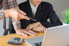 Bedrijfsmensenpunten aan een computer die iets verklaren aan een wisselmarkt stock afbeelding