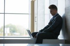 Bedrijfsmensenzitting alleen op een bank met laptop Royalty-vrije Stock Foto's