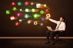 Bedrijfsmensenzitting als bureauvoorzitter met laptop en kleurrijke ap Stock Fotografie