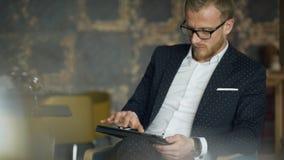 Bedrijfsmensenzitting in een restaurant en kliks op de tablet stock videobeelden