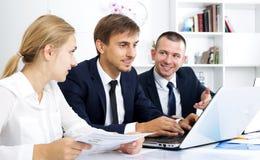 Bedrijfsmensenzitting met laptop op bureau Royalty-vrije Stock Afbeelding