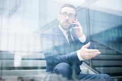 Bedrijfsmensenzitting op stappen die smartphone spreken royalty-vrije stock afbeeldingen