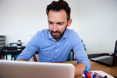 Bedrijfsmensenzitting op zijn kantoor en het werken aan laptop Royalty-vrije Stock Afbeelding