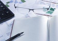 Bedrijfsonderzoek Notitieboekje met vulpen, calculator, glazen op rapporten en document met cijfers, grafieken royalty-vrije stock afbeeldingen