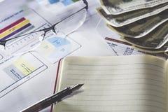 Bedrijfsonderzoek Notitieboekje met vulpen, dollarbankbiljetten, glazen op rapporten en document met cijfers, grafieken stock foto's