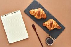 Bedrijfsontbijt van twee Franse croissants met blocnote Royalty-vrije Stock Afbeeldingen