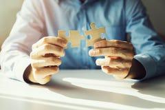 Bedrijfsoplossingen - zakenman verbindende puzzel stock fotografie