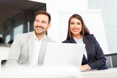 Bedrijfspaar die aan project op modern kantoor samenwerken stock foto