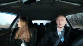 Bedrijfspaar die in de auto met de telefoon werken stock video