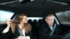 Bedrijfspaar die in de auto met de telefoon werken stock videobeelden