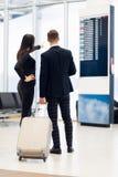Bedrijfspaar die de instapkaart van de tijdschemaholding bij de luchthaven bekijken stock afbeelding