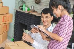 Bedrijfspaar die voorraad in hun online huiszaken controleren stock foto's