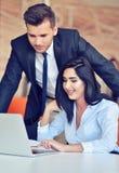 Bedrijfspaar in een bureau die aan de computer werken royalty-vrije stock afbeelding