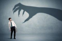Bedrijfspersoon bang van een groot de schaduwconcept van de monsterklauw Stock Foto's