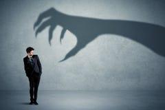 Bedrijfspersoon bang van een groot de schaduwconcept van de monsterklauw Stock Fotografie