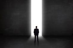 Bedrijfspersoon die muur met het lichte tunnel openen bekijken Royalty-vrije Stock Foto