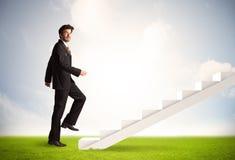 Bedrijfspersoon die omhoog op witte trap in aard beklimmen Royalty-vrije Stock Afbeeldingen