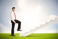 Bedrijfspersoon die omhoog op witte trap in aard beklimmen Stock Afbeelding