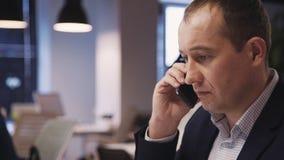 Bedrijfspersoon die op cellulair over vergadering in bedrijf spreken stock video