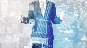 Bedrijfspersoon die zich met cityscape op de achtergrond bevinden royalty-vrije stock afbeelding