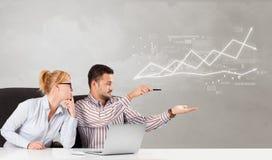 Bedrijfspersoonszitting bij bureau met financieel veranderingsconcept royalty-vrije stock foto