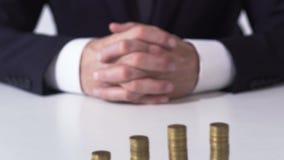 Bedrijfspersoonszitting voor muntstukstapels, bankwezen en inkomen het groeien stock video