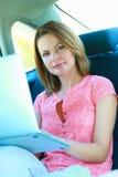 Bedrijfsreis: bezige onderneemster met laptop in auto Royalty-vrije Stock Afbeeldingen