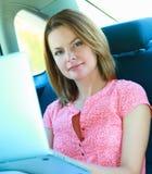 Bedrijfsreis: bezige onderneemster met laptop in auto Stock Foto's