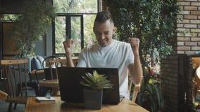 Bedrijfssucces - gelukkige stafmedewerker met laptop computer het vieren succesvoltooiing Mens die in koffie werkt stock videobeelden