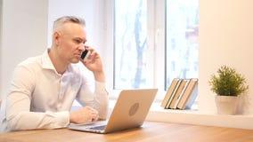 Bedrijfstelefoonbespreking op het Werk door de Middenleeftijdsmens stock video