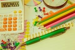 Bedrijfstoebehorenpotlood, calculator, vulpen en grafiek, lijsten, grafieken op een houten bureau Stock Foto