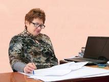 Bedrijfsvrouw achter het bekijken van de tekeningen. Stock Foto