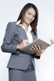 Bedrijfsvrouw Aziatische aantrekkelijke status gebruikend een pen het schrijven dia Stock Afbeelding