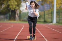 Bedrijfsvrouw in beginpositie klaar te lopen en sprint op atletiek het rennen spoor stock afbeelding