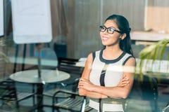 Bedrijfsvrouw bij bureauvenster stock afbeeldingen