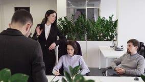 Bedrijfsvrouw die aan haar collega's bij werkplaats in bureau spreken stock videobeelden