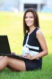 Bedrijfsvrouw die aan laptop buiten in park werken stock foto's