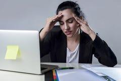 Bedrijfsvrouw die aan laptop op kantoor in spanning werken die aan intense hoofdpijnmigraine lijden Royalty-vrije Stock Foto's