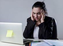 Bedrijfsvrouw die aan laptop op kantoor in spanning werken die aan intense hoofdpijnmigraine lijden Stock Afbeelding